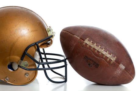 uniforme de futbol: Un casco de f?tbol americano y f?tbol retro sobre un fondo blanco Foto de archivo