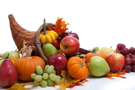 cuerno de la abundancia: Una cornucopia rebosante incluyendo calabazas, uvas, calabazas y hojas sobre un fondo blanco