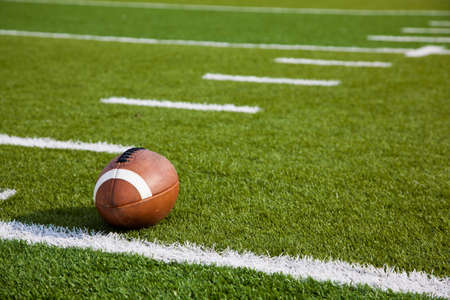 緑のサッカーのフィールドにアメリカン フットボール