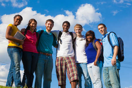 A group of diverse college students friends outside on a hill with a sky background photo