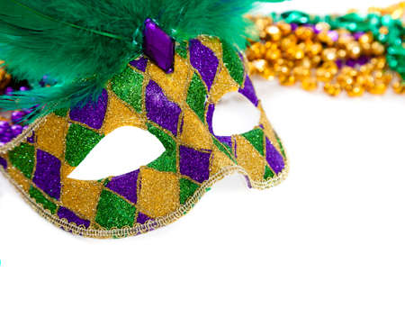 A purple, gold and green mardi gras mask and beads on white Stockfoto