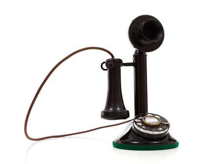 antique phone: A black vintage candlestick phone on a white background with copyspace Stock Photo