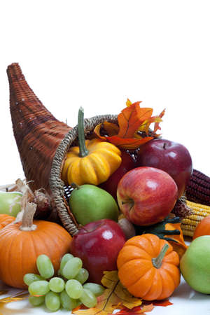 horn of plenty: An overflowing cornucopia including pumpkins, grapes, gourds and leaves on a white background
