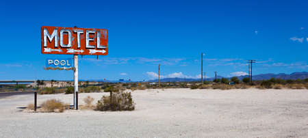 A vintage neon motel sign in the desert with a sky blue background photo