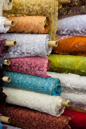 A background of rolls of various colored fabric