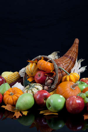 An overflowing cornucopia including pumpkins, grapes, gourds and leaves on a black background photo