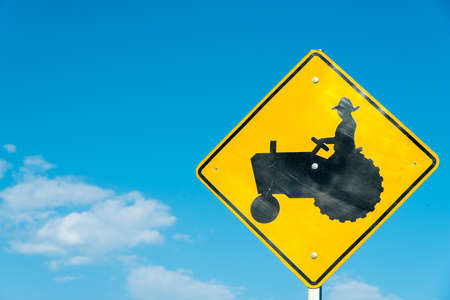 tractor warning sign: A yellow tractor crossing sign with a sky blue background