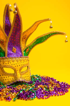 A festive, colorful group of mardi gras or carnivale mask on a yellow background   Venetian masks  Stock Photo