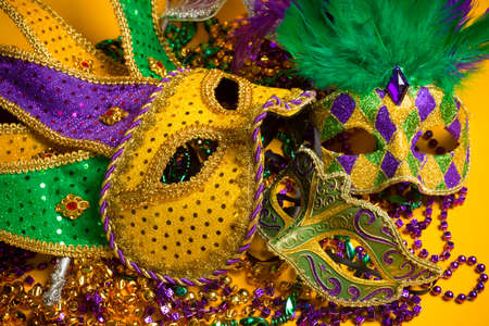 mardigras: A festive, colorful group of mardi gras or carnivale mask on a yellow background   Venetian masks  Stock Photo