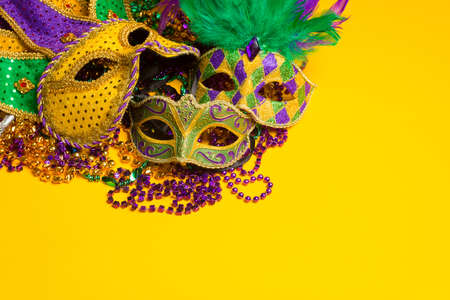 A festive, colorful group of mardi gras or carnivale mask on a yellow background   Venetian masks  Stok Fotoğraf