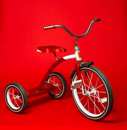 antique tricycle: A vintage red tricycle on a bright red background