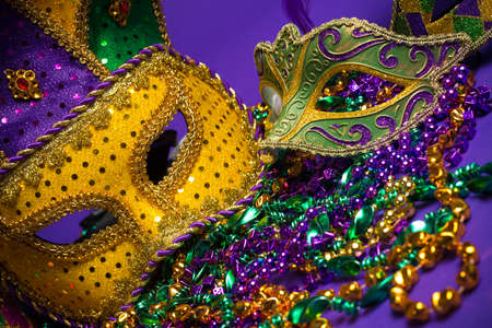a beads: Festive Grouping of mardi gras, venetian or carnivale mask on a purple background