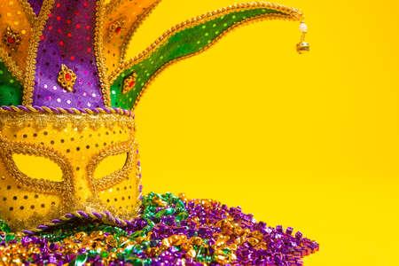 マルディグラやカーニバル マスク黄色の背景のベネチアン マスク上のお祝い、カラフルなグループ 写真素材