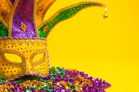 A festive, colorful group of mardi gras or carnivale masks on a yellow background   Venetian masks  photo