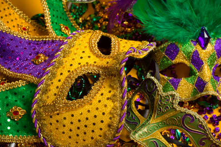 mardigras: A festive, colorful group of mardi gras or carnivale masks on a yellow background   Venetian masks
