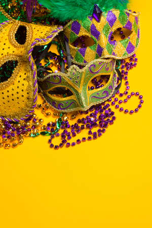 A festive, colorful group of mardi gras or carnivale masks on a yellow background   Venetian masks