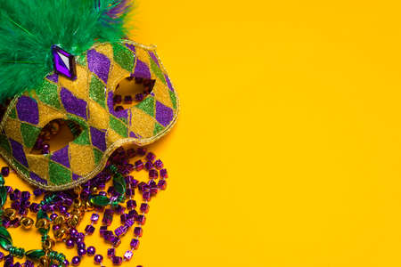 A festive, colorful mardi gras or carnivale mask on a yellow background   Venetian mask