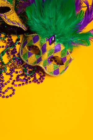 黄色の背景のベネチアン マスクに陽気でカラフルな mardi gras または carnivale マスク