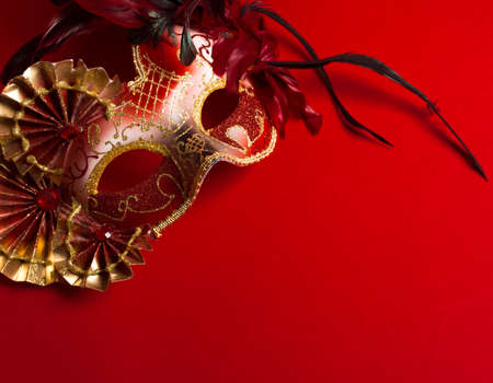 mardi gras background: A red and gold venetian, mardi gras mask on a red bakground Stock Photo