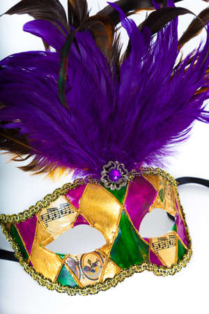 A purple, gold, yellow and purple mardi gras or venetian mask on a white  Stock Photo