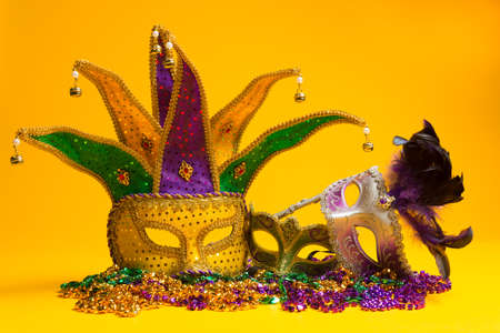 A festive, colorful group of mardi gras or carnivale mask on a yellow .  Venetian masks. photo