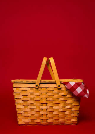 picnic tablecloth: A brown, wicker picnic basket with red gingham tablecloth on a red with copy space