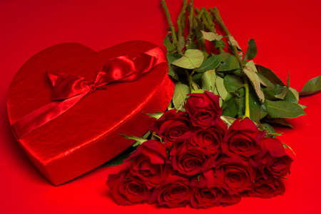 dozen: a dozen long stemmed red Roses and a red heart box on a red background Stock Photo