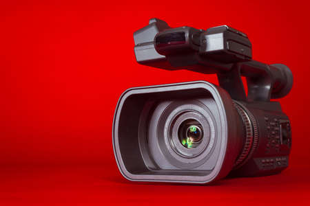 A black video camera on a red background with copy space photo