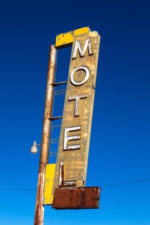 decrepit: A vintage, neon, decrepit motel sign with a sky background
