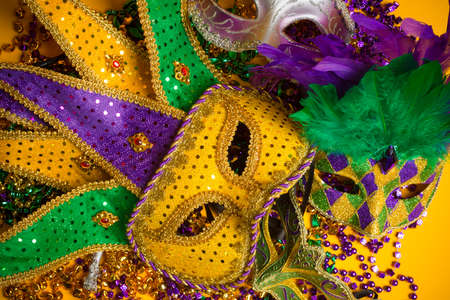 mardi gras background: A festive, colorful group of mardi gras or carnivale mask on a yellow background.  Venetian masks.