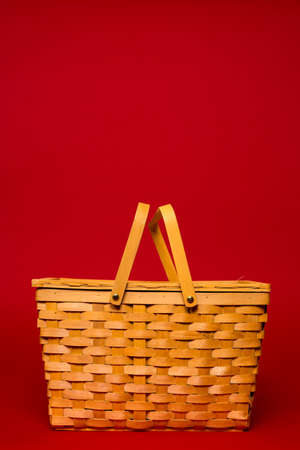 pic nic: A brown wicker basket on a red background with copy space