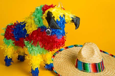 traje mexicano: Una piñata torro mexicano y sombrero sobre un fondo amarillo