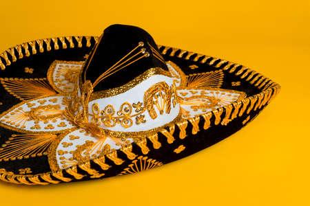 Negro adornado, dorado y blanco sombrero mexicano sobre un fondo de color amarillo brillante Foto de archivo - 27494742