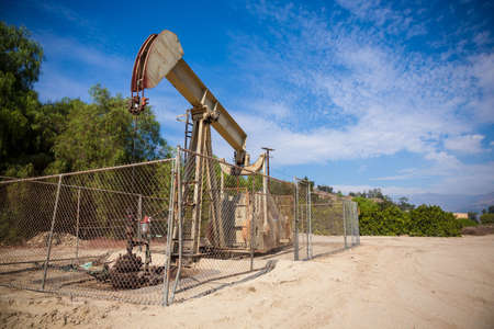 pumpjack: A horsehead pumpjack with a blue sky background with clouds Stock Photo