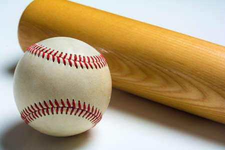 A wooden baseball bat and ball on a white