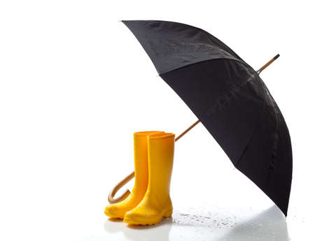A pair of yellow rainboots and a black umbrella