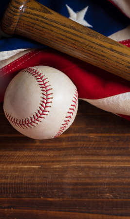 An old, antique American flag with vintage baseball equipment on a wooden bench Reklamní fotografie - 44669561