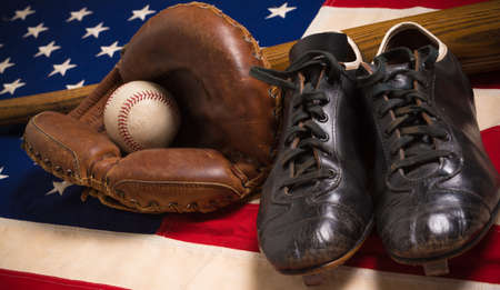 old flag: An old, antique American flag with vintage baseball equipment on a wooden bench