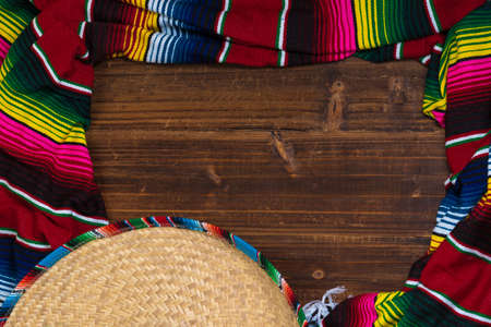 hispanics mexicans: A traditional Mexican Sombrero and serape blanket on a wooden background with copy space