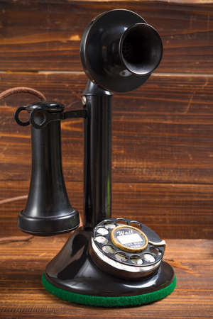 old fashioned: A vintage, old-fashioned, antique candlestick telephone on a wood background