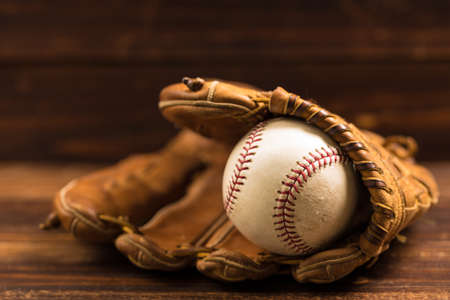 baseball glove: Brown leather baseball glove on a wooden bench