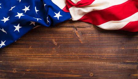 Uma bandeira americana velha em uma plataforma de madeira antiga com espaço da cópia