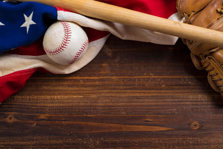 An old, antique American flag with vintage baseball equipment on a wooden bench