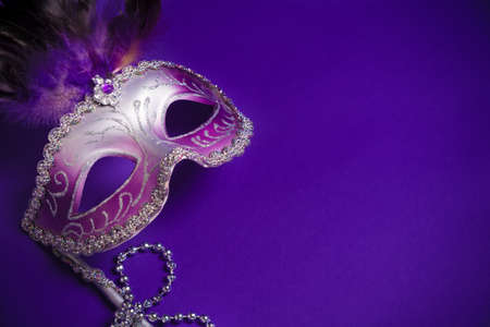 carnivale: A purple mardi gras mask on a purple background with beads.  Carnivale costume. Stock Photo