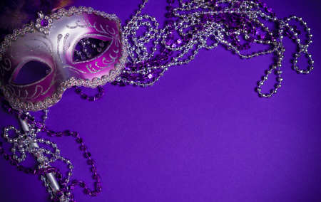 A purple mardi gras mask on a purple background with beads.  Carnivale costume. Stock Photo