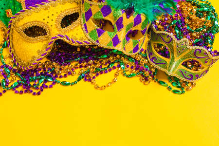 A venetian, mardi gras mask or disguise on a yellow background Stockfoto