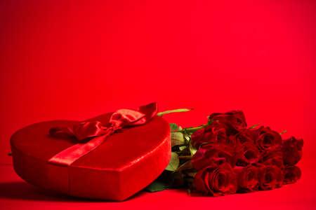 rosas rojas: Una caja del caramelo de San Valent�n y rosas rojas sobre fondo rojo