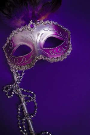 Een paarse mardi gras masker op een paarse achtergrond met parels. Carnivale kostuum.