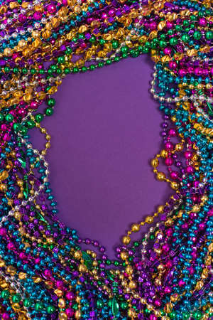 A background of mardi gras beads with copy space