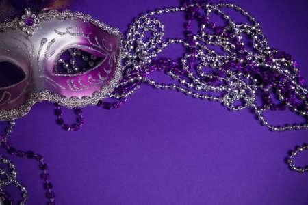 A purple mardi gras mask on a purple background with beads.  Carnivale costume. Archivio Fotografico